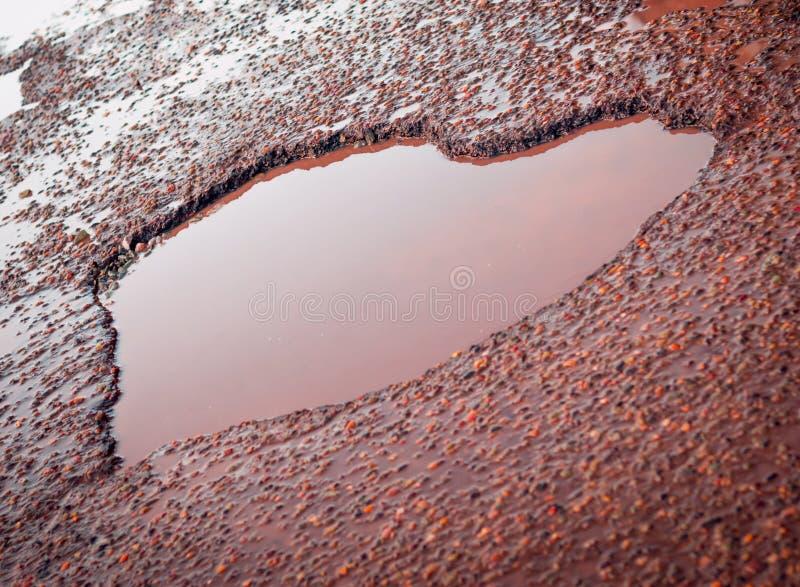 Buca a forma di in Asphalt Road With Puddles anziano, ghiaia, pietre del cuore Segno di amore fotografia stock libera da diritti