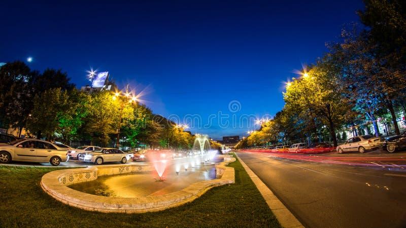 Bucareste centra o tiro da noite do tráfego nas fontes fotografia de stock