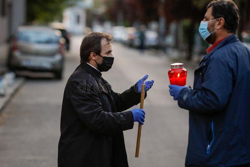 Bucareste, Romênia - 18 de abril de 2020: Um padre ortodoxo usando luvas e máscara devido ao bloqueio pandêmico de 19 de setembro imagens de stock royalty free