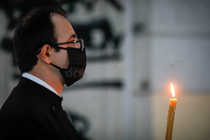 Bucareste, Romênia - 18 de abril de 2020: Um padre ortodoxo usando luvas e máscara devido ao bloqueio pandêmico de 19 de setembro fotografia de stock royalty free