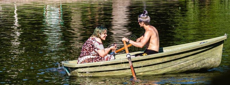 Bucareste, Rom?nia - 2019 Retrato de pares novos no amor que fala quando esporte de barco do pedal no lago Homem e mulher alegres fotos de stock royalty free
