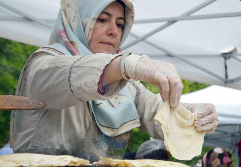Bucareste, Romania 22 de maio de 2016 A mulher turca supervizes o processo de cozimento de um pão liso tradicional em um forno do fotos de stock