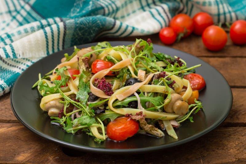 Bucatini italiano com camarão, rúcula e tomates de cereja Fundo de madeira Close-up Vista superior imagens de stock