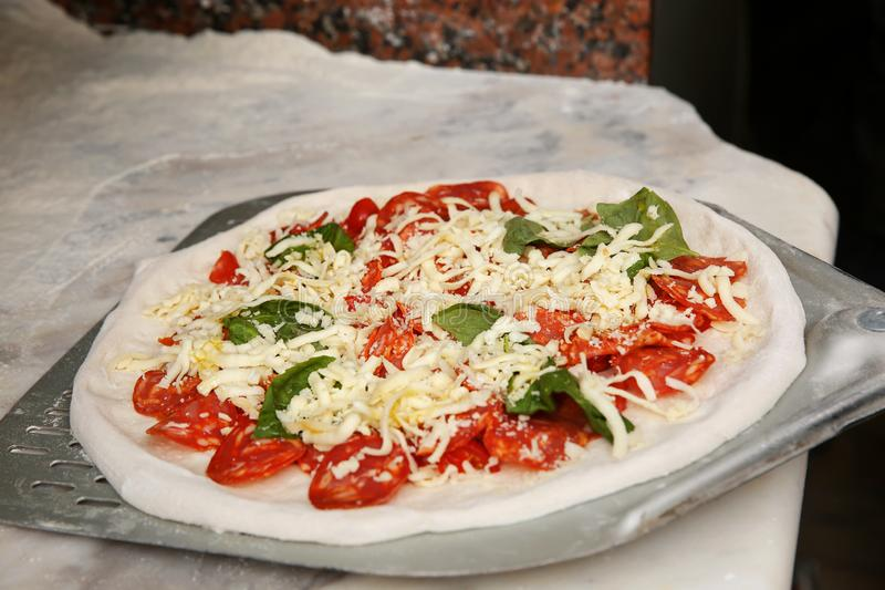 Buccia con pizza italiana tradizionale cruda nella cucina del ristorante immagini stock libere da diritti