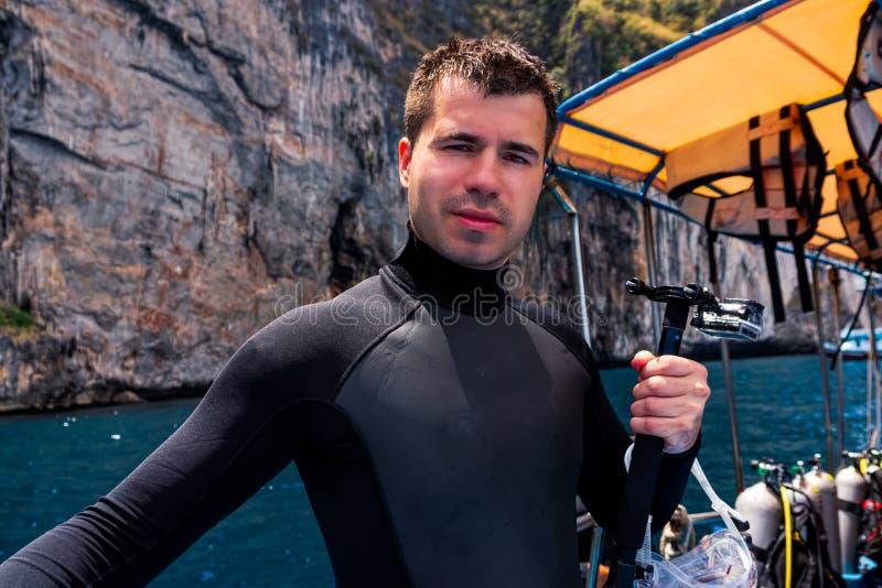 Buceador de sexo masculino que sostiene la cámara de la acción y que se prepara para zambullirse, Phi Phi Island imagen de archivo