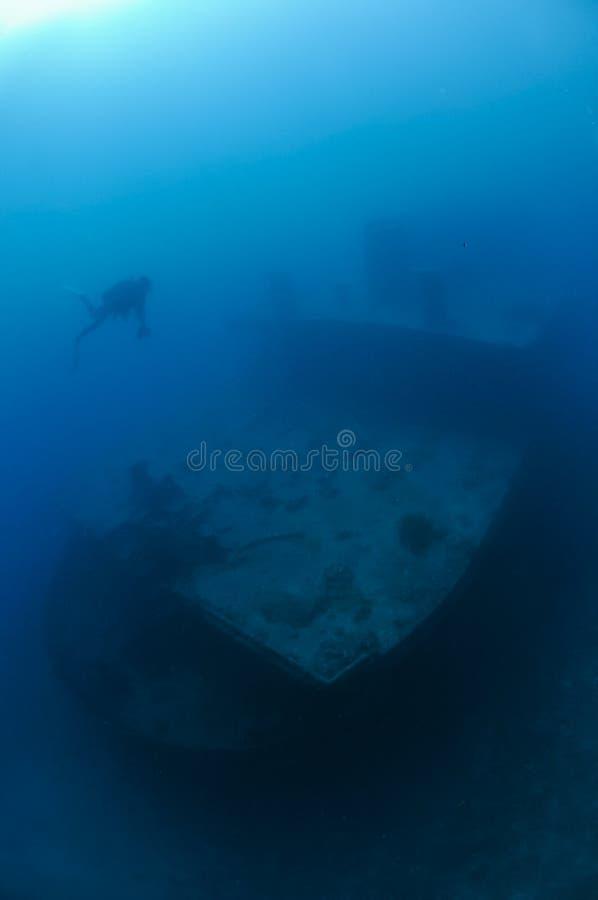 Buceador Diving hacia la nave hundida fotos de archivo