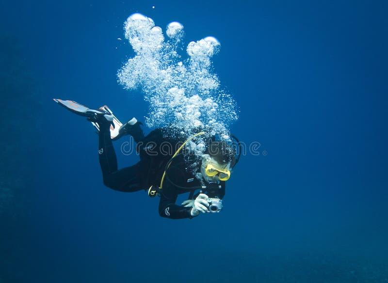 Buceador que toma la foto subacuática en agua azul profunda fotos de archivo libres de regalías