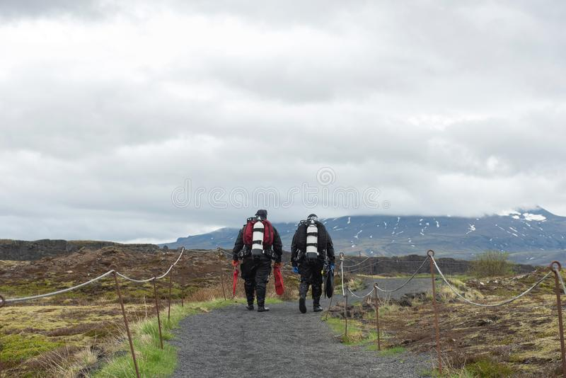 Buceadores que caminan en el equipo de buceo lleno en Silfra, Islandia imágenes de archivo libres de regalías