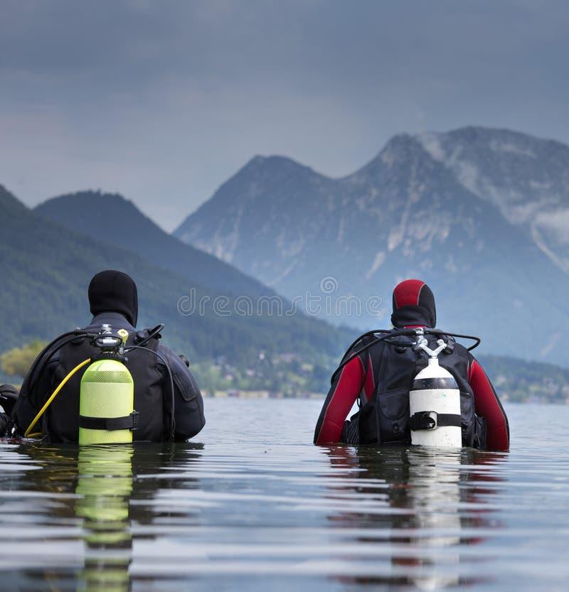 Buceadores que inscriben el agua en el lago de la montaña fotos de archivo