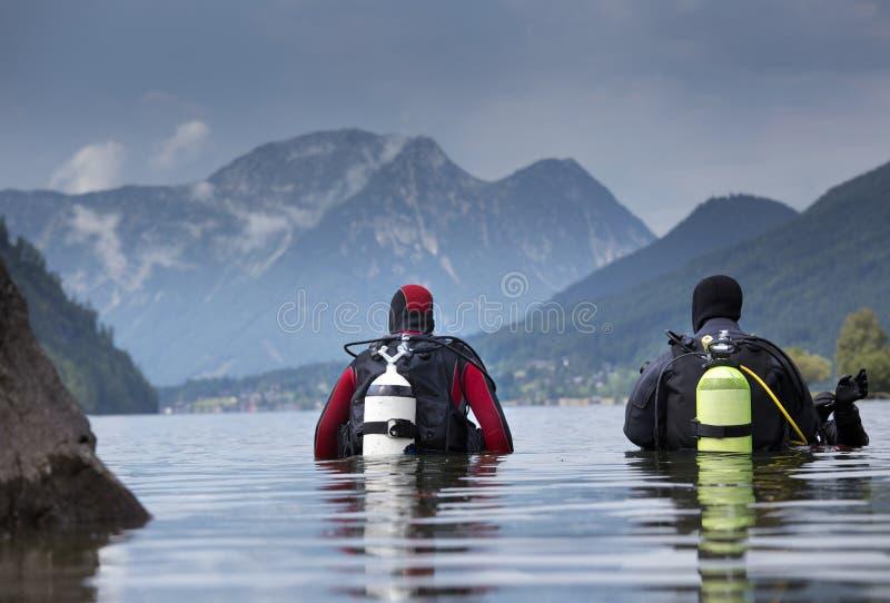 Buceadores que inscriben el agua en el lago de la montaña imagen de archivo libre de regalías