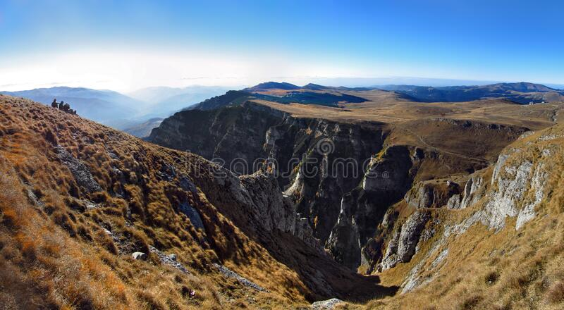 Bucegi mountains high altitude panorama, steep heels in autumn. Climbers resting on steep cliff and admire the landscape. Bucegi mountains panorama, Romania royalty free stock images