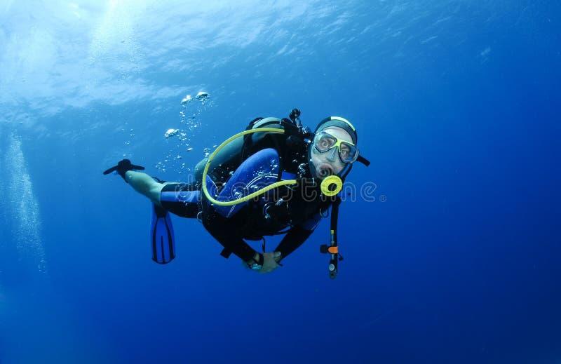 Buceo con escafandra en agua azul clara fotos de archivo