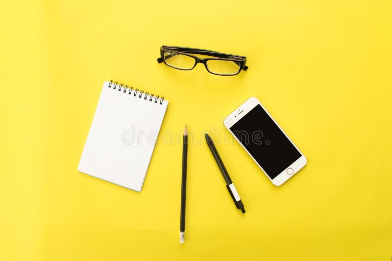 Buch-, Bleistift-, Stift-, Smartphone- und Augengläser auf gelbem Hintergrund Lebensstilarbeitsplatz, Draufsicht stockbilder
