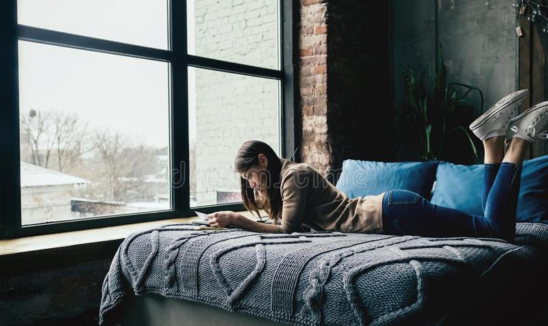 Buch der jungen Frau, das auf Betthaus liegt stockbild