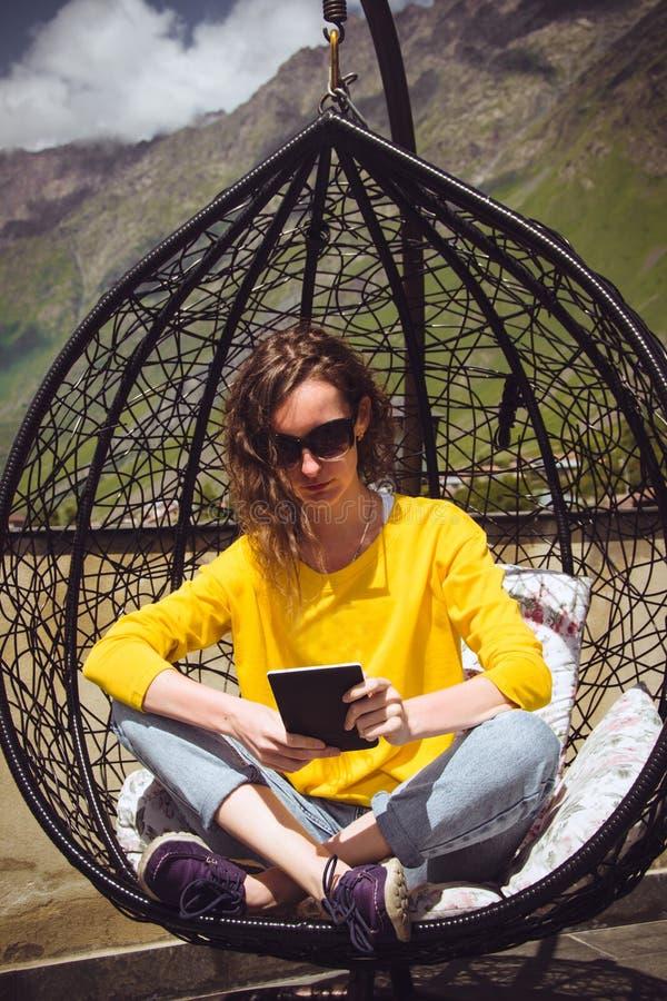Buch der jungen Frau Leseauf digitalem Gerät Tablet compuer Hippie-Mädchen, das gekreuzte Beine in hängendem Stuhl des Aufenthalt stockbild