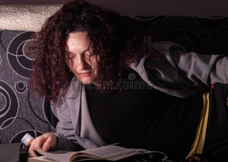 Buch der jungen Frau Leseauf einem Sofa in einer Dunkelkammer stockbild