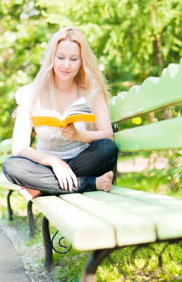 Buch der jungen Frau Leseim Park lizenzfreies stockfoto