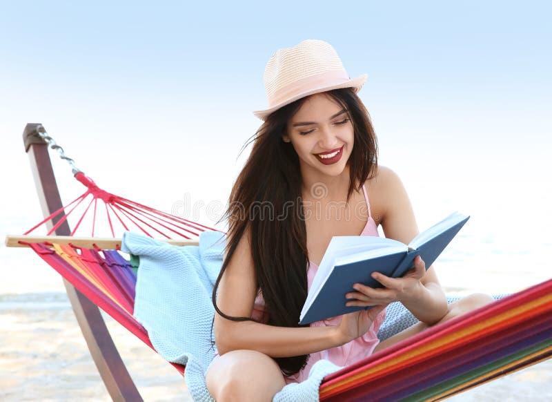 Buch der jungen Frau Lesein der Hängematte stockbilder