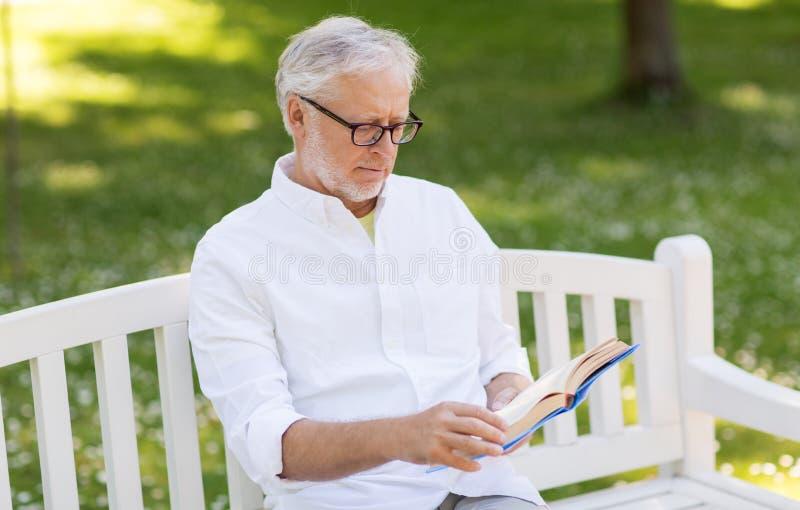 Buch des älteren Mannes Leseam Sommerpark stockbild