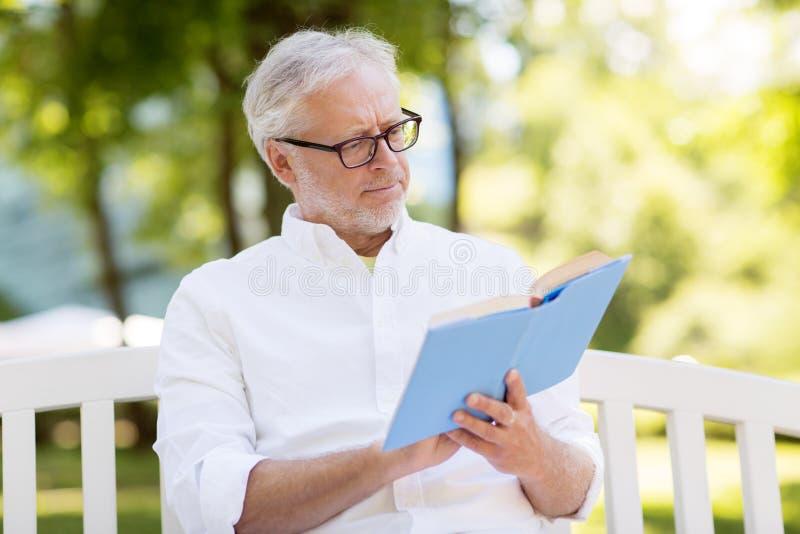 Buch des älteren Mannes Leseam Sommerpark lizenzfreies stockfoto