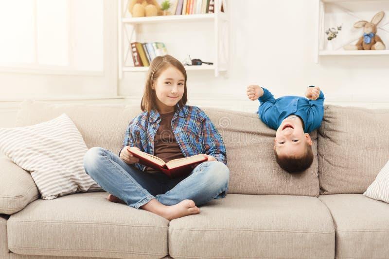 Buch des jungen Mädchens Lesefür ihren Bruder lizenzfreie stockbilder