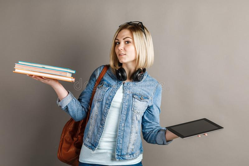 Buch gegen EBook Studentin, die ein traditionelles Lehrbuch hält und stockfotos