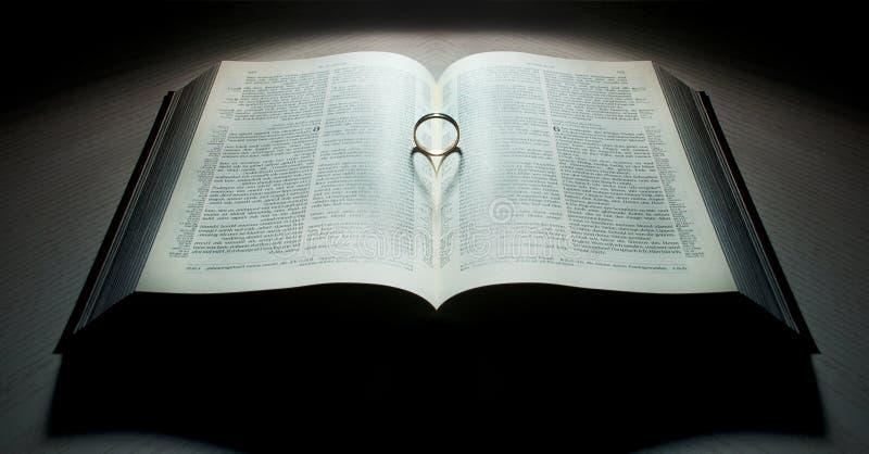 Buch mit einem Herz-förmigen Ring stockfotografie