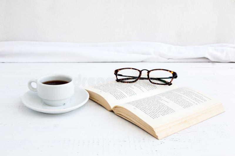 Buch mit Gläsern auf weißem Holztisch stockfotografie