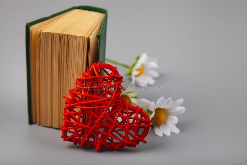 Buch mit romantischen Gedichten, Blumen und einem Herzen stockfotografie