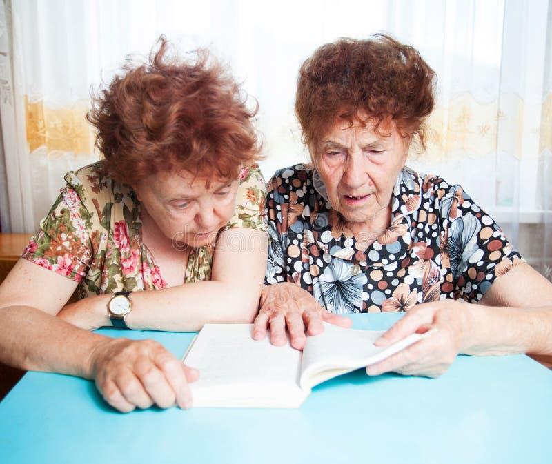 Buch mit zwei Senioren Lese stockfotos