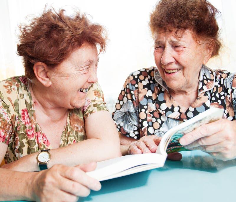 Buch mit zwei Senioren Lese stockbilder