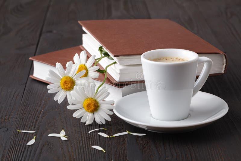 Buch und daisie Blume auf Holztisch stockbilder