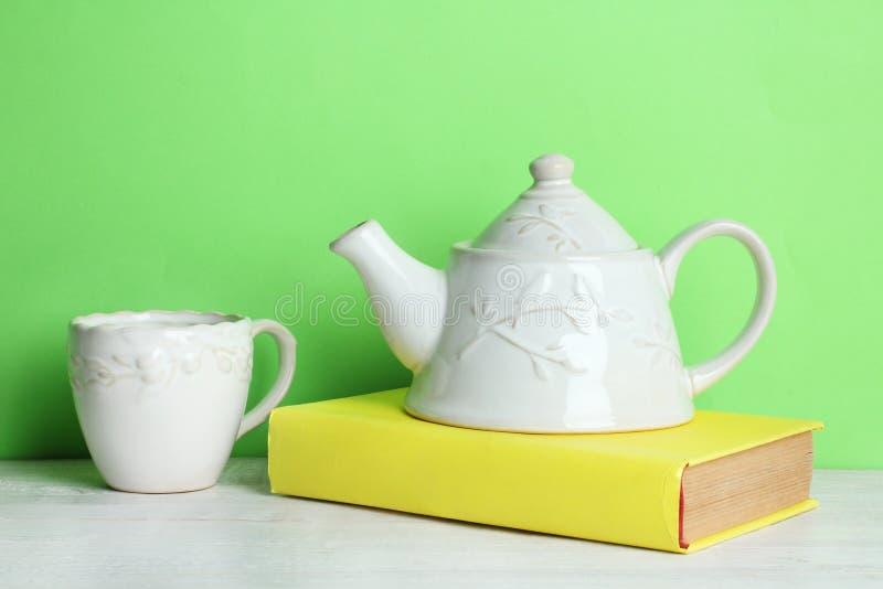 Buch und Teekanne mit einer Schale stockfotografie