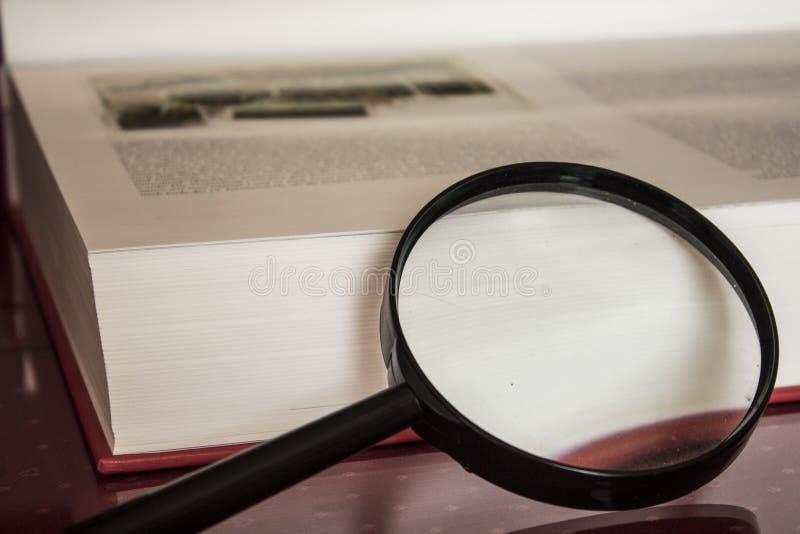 Buch und Vergrößerungsglas lizenzfreies stockbild