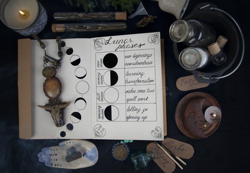 Buch von Schatten mit Mondphasen auf schwarzem Altar lizenzfreies stockbild