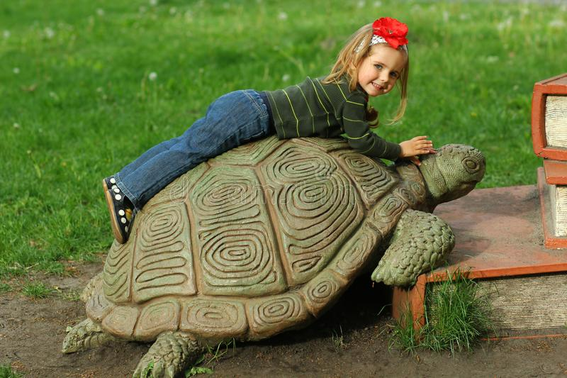 Bucha, Ukraine - 6 May, 2018: Book festival in the public park, toddler girl lying on a giant turtle climbing on a giant pile of b. Ooks, education knowledge royalty free stock photo