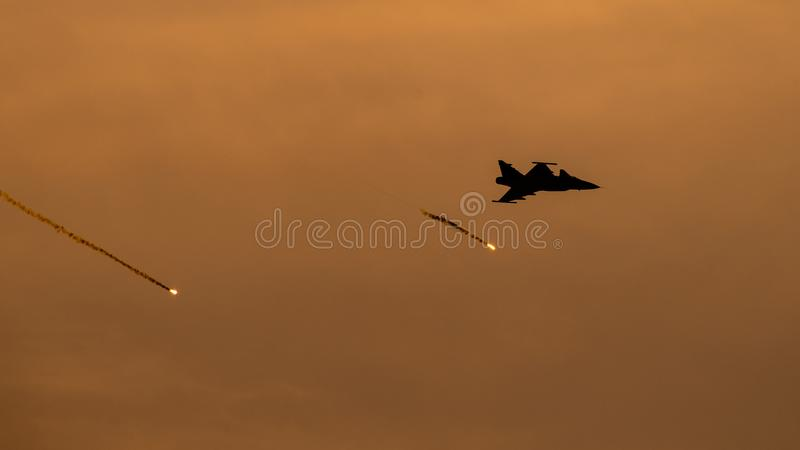 Bucharest international air show BIAS, F16 silhouette with decoy flares royalty free stock photo