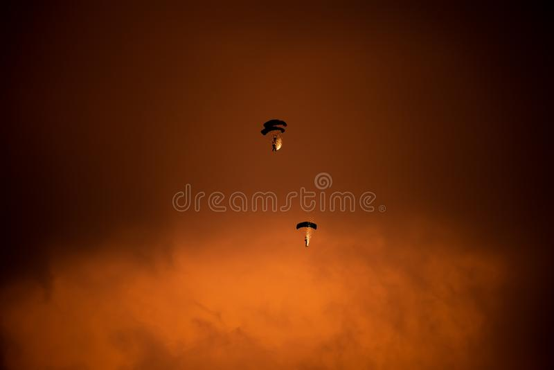 Bucharest international air show BIAS, parachute silhouette with sparks on sunset sky stock photography