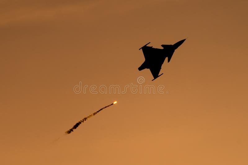 Bucharest international air show BIAS, Saab 9 Gripen silhouette with flares royalty free stock image