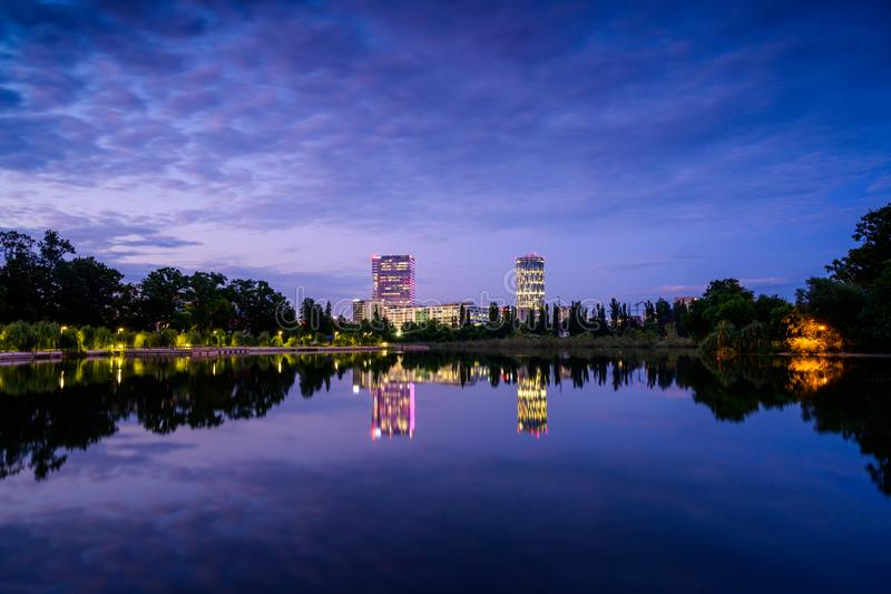Bucharest office buildings at blue hour with lake reflection in summer time , Romania royalty free stock photography