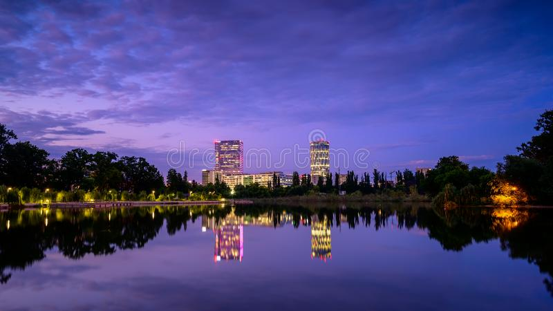 Bucharest office buildings at blue hour with lake reflection in summer time , Romania.  royalty free stock photo