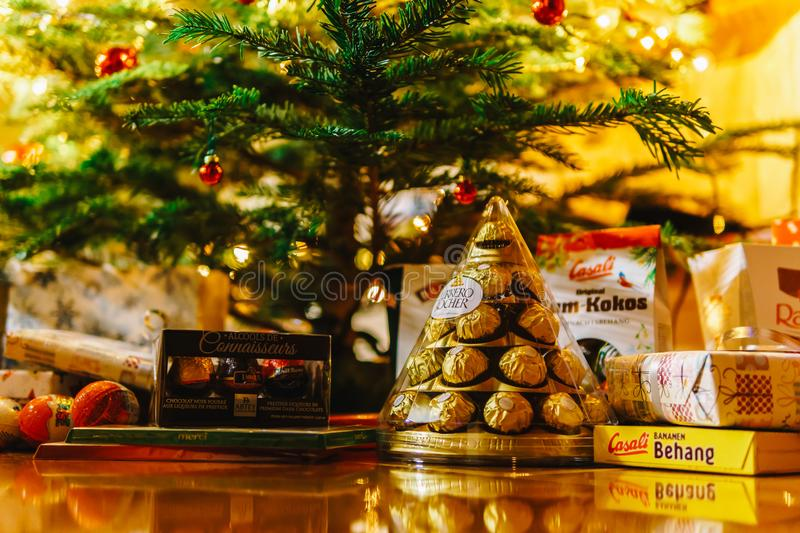 Presents And Chocolate Candies Waiting To Be Opened Under Christmas Tree royalty free stock photo