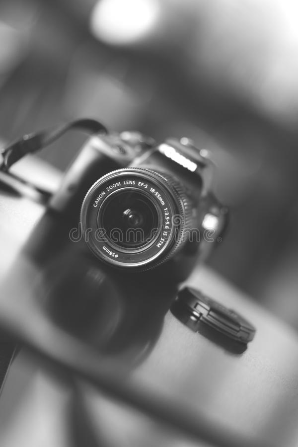 Professional Canon DSLR camera with factory lens on a table in black and white. Bucharest, Romania - January 1, 2020: Professional Canon DSLR camera with factory royalty free stock image