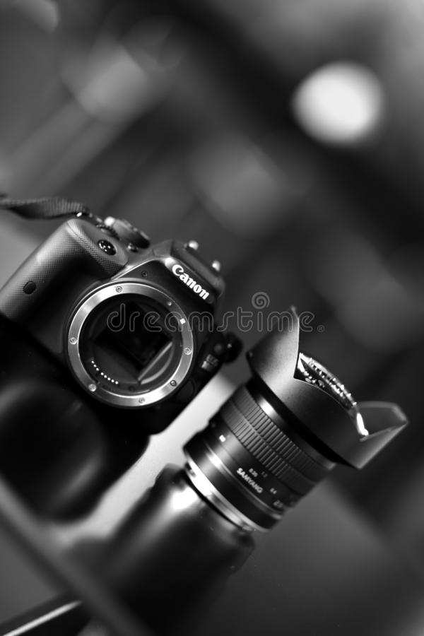 Professional Canon DSLR camera with Samyang ultrawide lens on a table in black and white. Bucharest, Romania - January 1, 2020: Professional Canon DSLR camera stock photo