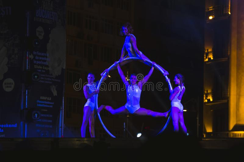 Sonics in Wish performance at Street Theater Festival in Bucharest. Graceful dancers on hula hoop circle royalty free stock photos