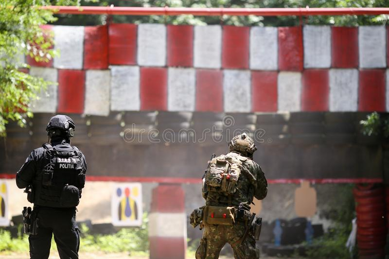 A Romanian SIAS equivalent of SWAT in the US police officer and a special forces soldier train together in a shooting range stock image