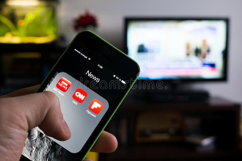 BUCHAREST, ROMANIA - NOVEMBER 21, 2014: Photo of hand holding an iphone with news apps on screen and tv set in the background with royalty free stock image