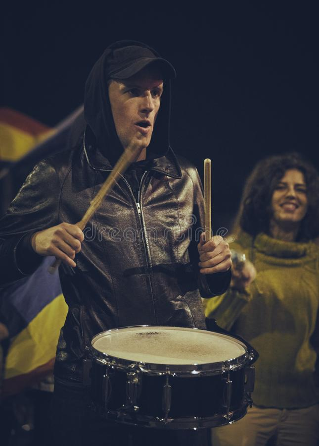 Protests against Rosia Montana gold mine, Bucharest, Romania. Bucharest, Romania - October 6, 2013: A protester loudly plays the drum during the population royalty free stock photo