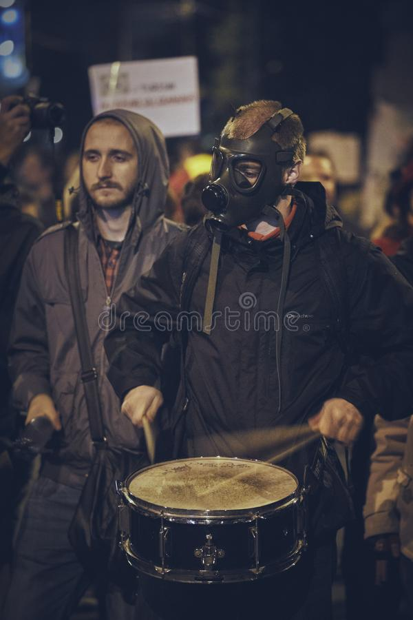 Protests against Rosia Montana gold mine, Bucharest, Romania. Bucharest, Romania - October 6, 2013: Young man wearing gas mask plays the drum during the rally stock photos