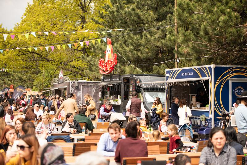 Bucharest, Romania: 21.04.2019 - Street Food Truck festival - People sitting and eating at their tables at a food. Festival in the park during a Sunday. Eating royalty free stock images